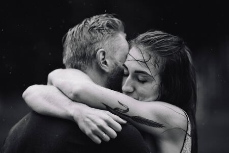 freedom woman: beautiful couple hugging on outside in the rain