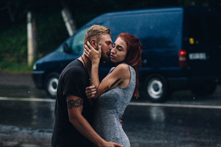 love in rain: beautiful couple hugging on outside in the rain
