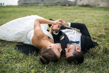 lovely women: Wedding couple lying on the grass in front of camera
