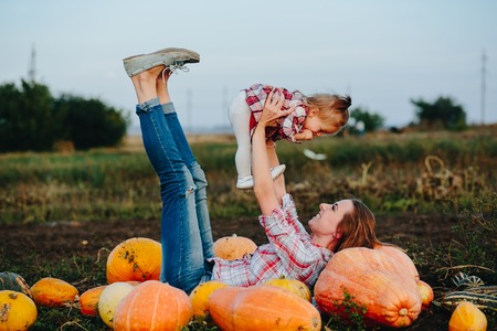 mother nature: mother and daughter lie between pumpkins on the field, Halloween eve