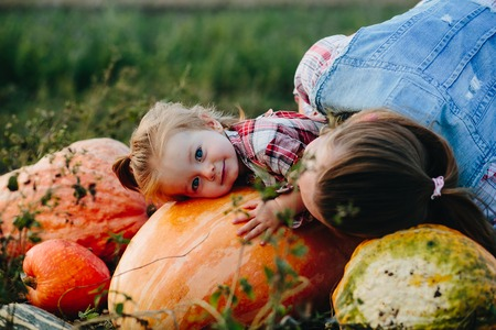 daughter lying on a pumpkin, and her mother standing beside, Halloween eve Banque d'images
