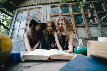Three vintage witches perform magic ritual, at the table, reading a magical book on the eve of Halloween Imagens