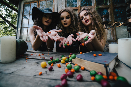 sibyl: Three vintage witches perform magic ritual, throwing sweet at a table on the eve of Halloween