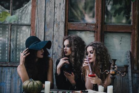 elixir: Tres brujas vendimia realizan ritual de magia, en la mesa, con el elixir de la mano en la víspera de Halloween de