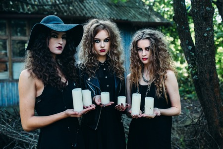 sibyl: three vintage women as witches, poses and hold in their hands the candles on the eve of Halloween