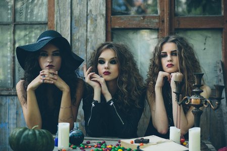 sibyl: three witches are sitting at a table on the eve of Halloween