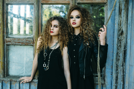 sibyl: two vintage women as witches, posing beside an abandoned building on the eve of Halloween