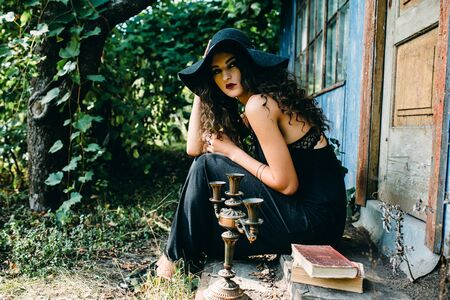 cast in place: Vintage woman as witch, posing beside an abandoned building on the eve of Halloween