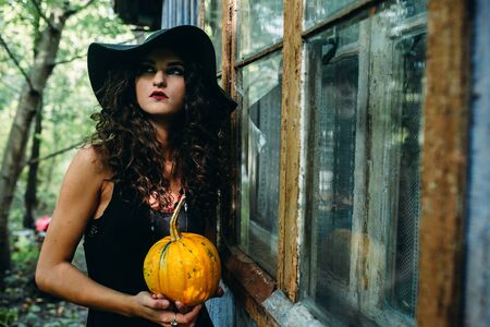 Vintage woman as witch posing with pumpkin in the hands against the backdrop of an abandoned place on the eve of Halloween Stock Photo