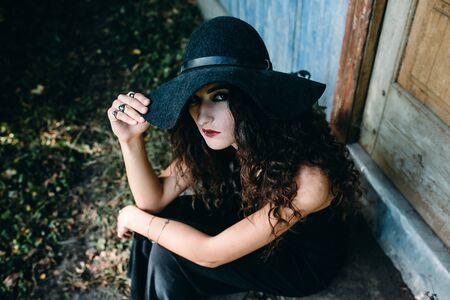 bruja: Mujer de la vendimia como bruja, posando junto a un edificio abandonado en la víspera de Halloween de