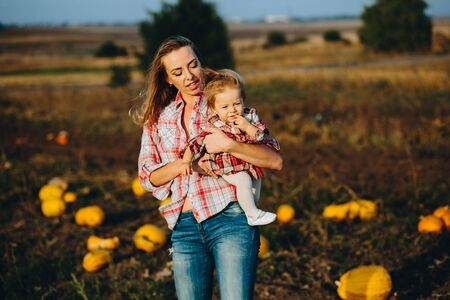 vegetare: mother and daughter on a field with pumpkins