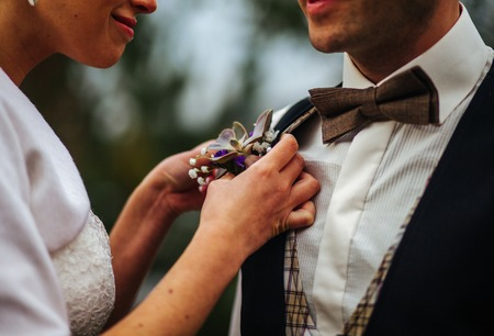 buttonhole: young woman adjusting boutonniere on groom suit