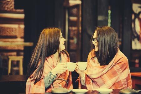 chismes: Dos chicas j�venes y hermosas que chismean en la terraza con una taza de caf�, el tono