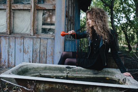 elixir: Vintage witch performs magical ritual, with elixir in hand on the eve of Halloween Foto de archivo