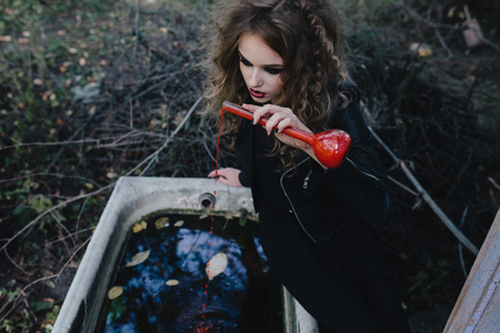 elixir: Bruja del vintage realiza ritual m�gico, con el elixir de la mano en la v�spera de Halloween de