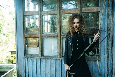 enchantress: Vintage woman as witch, posing against the backdrop of an abandoned place on the eve of Halloween
