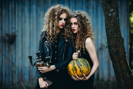 two vintage women as witches, posing in front of an abandoned house on the eve of Halloween