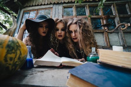sibyl: Three vintage witches perform magic ritual, at the table, reading a magical book on the eve of Halloween Stock Photo