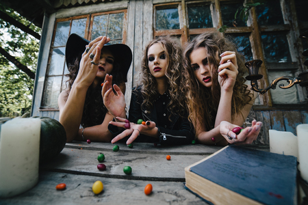 Three vintage witches perform magic ritual, throwing sweet at a table on the eve of Halloween