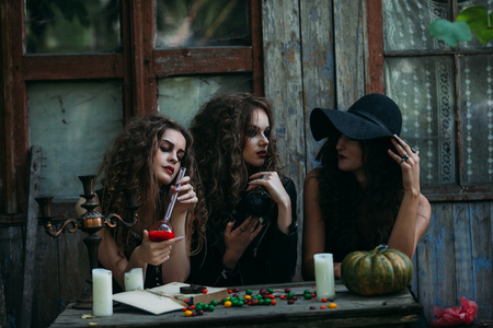 sibyl: Three vintage witches perform magic ritual, at the table, with the elixir in hand on the eve of Halloween