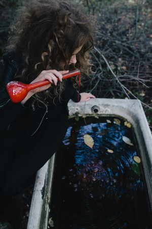 elixir: Vintage witch performs magical ritual, with elixir in hand on the eve of Halloween Stock Photo
