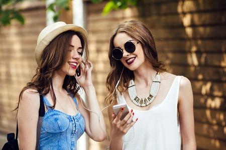 parejas jovenes: Dos hermosas chicas j�venes est�n caminando por la ciudad y escuchar m�sica Foto de archivo