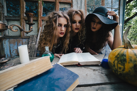 Three vintage witches perform magic ritual, at the table, reading a magical book on the eve of Halloween Stock Photo - 47226473