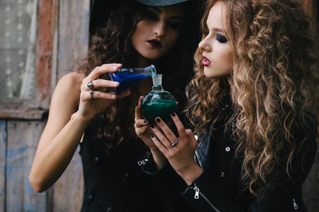 elixir: Two vintage witches perform magic ritual, with elixir in hand on the eve of Halloween