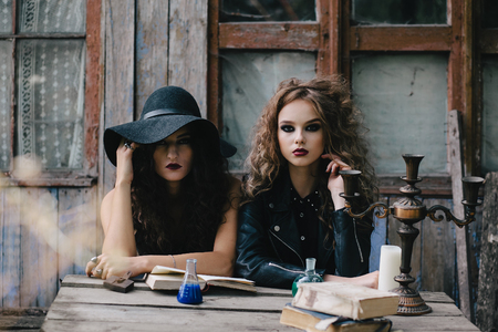 beldam: Two vintage witches perform magic ritual, with elixir in hand on the eve of Halloween