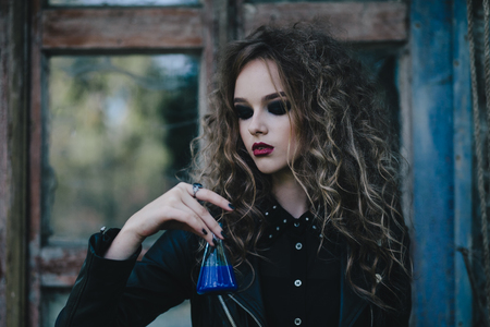 sibyl: Vintage witch performs magical ritual, with elixir in hand on the eve of Halloween Stock Photo
