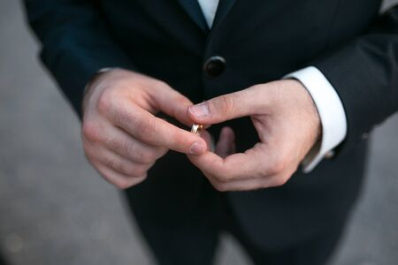 ring stand: groom holding a wedding ring and waits for bride Stock Photo