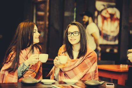 jeune fille: Deux jeunes et jolies filles bavardent sur la terrasse avec une tasse de caf�, Instagram ton Banque d'images