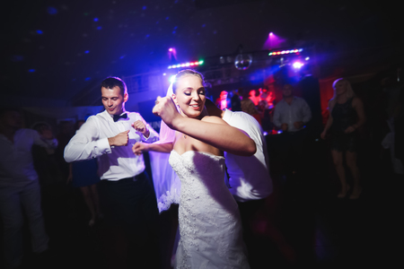 wedding party: beautiful bride and groom dancing among the people on the dance floor