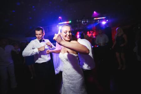 persone che ballano: bella sposa e sposo ballare tra la gente sulla pista da ballo