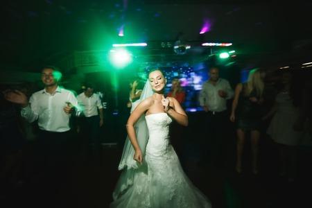 美しい花嫁と新郎のダンス ・ フロアで踊る人々 の間で 写真素材