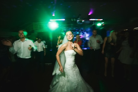 beautiful bride and groom dancing among the people on the dance floor