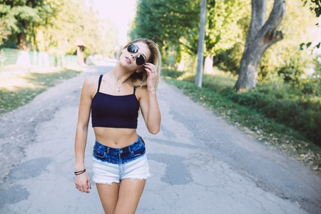street wise: beautiful girl walking down a forest road in solitude, sunny, summer day