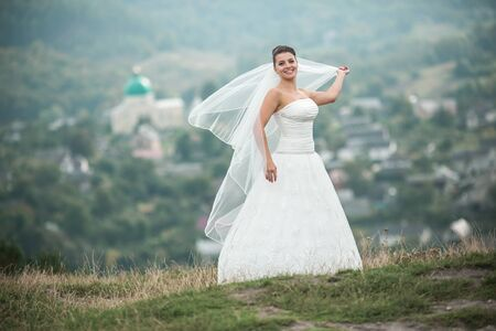 beautiful young bride poses for the camera on the background of the city in the distance Stock Photo