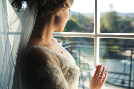 glamour girl: bride looking through the window from the hotel room Stock Photo