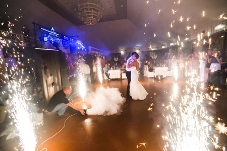 beautiful bride and groom dancing the first dance between fireworks