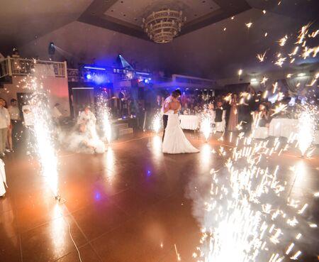 mooie bruid en bruidegom dansen de eerste dans tussen vuurwerk