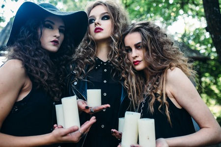three vintage women as witches, poses and hold in their hands the candles on the eve of Halloween