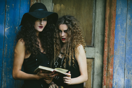 sibyl: Two vintage witch reading a book on the eve of Halloween in front of an abandoned house