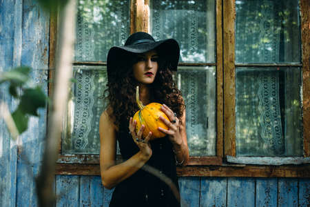 cast in place: Vintage woman as witch posing with pumpkin in the hands against the backdrop of an abandoned place on the eve of Halloween Stock Photo