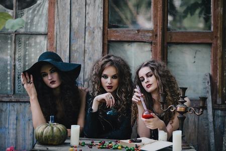 elixir: Tres brujas vendimia realizan ritual de magia, en la mesa, con el elixir de la mano en la v�spera de Halloween de