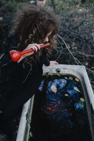 beldam: Vintage witch performs magical ritual, with elixir in hand on the eve of Halloween Stock Photo