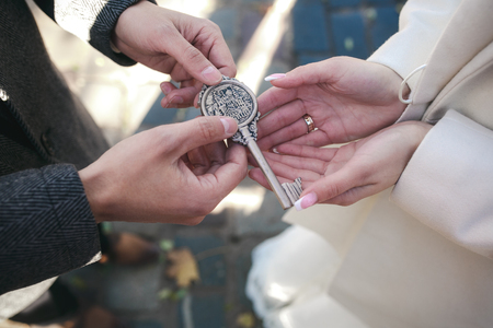 key: The lock with keys in hands of the groom and the bride Stock Photo