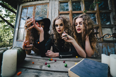 beldam: Three vintage witches perform magic ritual, throwing sweet at a table on the eve of Halloween