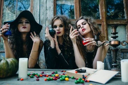 sibyl: three witches are sitting at the table and prepared the potion on the eve of Halloween