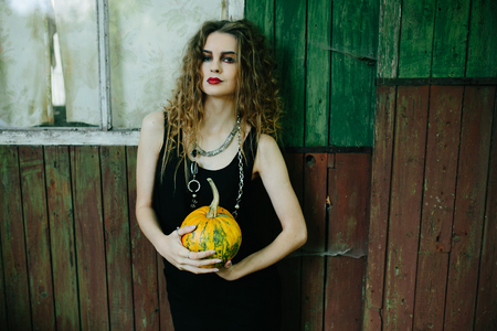 sibyl: Vintage woman as witch, posing against the backdrop of an abandoned place on the eve of Halloween